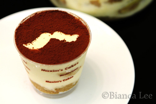 Banana Tiramisu Recipe- makes one 8 in cake + a few leftover glasses Lady finger sponge (this is only the sponge layer, so not the lady finger pieces, which you buy) (not essential btw, for a cake its better, for spoon out tiramisu from pudding cup or a bowl then no need) 70g egg whites 70g sugar 100g yolks 60g flour 30g cornstarch 30ml oil Beat egg whites with sugar until stiff peak Add yolks, sift in flour, cornstarch, fold into egg mixture. Fold in oil. Pour into 8in cake mould, and bake at 210C for 10min. Cool, slice into two layers. Ingredients for tiramisu 1 lady finger sponge (the cake that can be made from ingredients above) One pack of lady fingers- 10 pcs around Warm coffee- 250ml. If you like stronger coffee taste, put more coffee beans 40 ml Amaretto (you can substitute this for marsala or kahlua, or a mixture of any of these together) (i put around 60 ml because i like a stronger alcohol taste) Mascarpone cheese 250g 4 egg yolks 4 egg whites 75g sugar  10g gelatin powder 325g already whipped cream to stiff peaks cocoa powder for dusting Banana filling 3 bananas 20g sugar 1/2 pc lemon zest (not mandatory) 40g butter 1/4tsp cinnamon 5g rum Banana filling:  cut bananas into small slices. Heat butter & sugar in pan. Fry banans w/ lemon zest, cinnamon, rum until light golden brown. Leave to cool and for later use. Beat mascarpone cheese and yolks Beat whites with sugar to soft peaks & dissolve gelatine powder in 100ml hot water. Fold whites, gelatine water, and whipped cream into mascarpone cheese. Mix warm coffee with amaretto and other alcohol if you have. Dip one slice of the lady finger into the coffee mixture so that it is soaked, but not so soaked that it will break. Place in bottom of cake mould, then cover with some cheese mixture. Add some banana filling. Dip some lady finger biscuits into coffee mixture then arrange on cheese mixture, put some banana filling and put another layer of dipped sponge cake. Spoon some mascarpone cheese mixture. Chill until set- around 2 hrs. Dust with cocoa powder- use stencils for patterns.