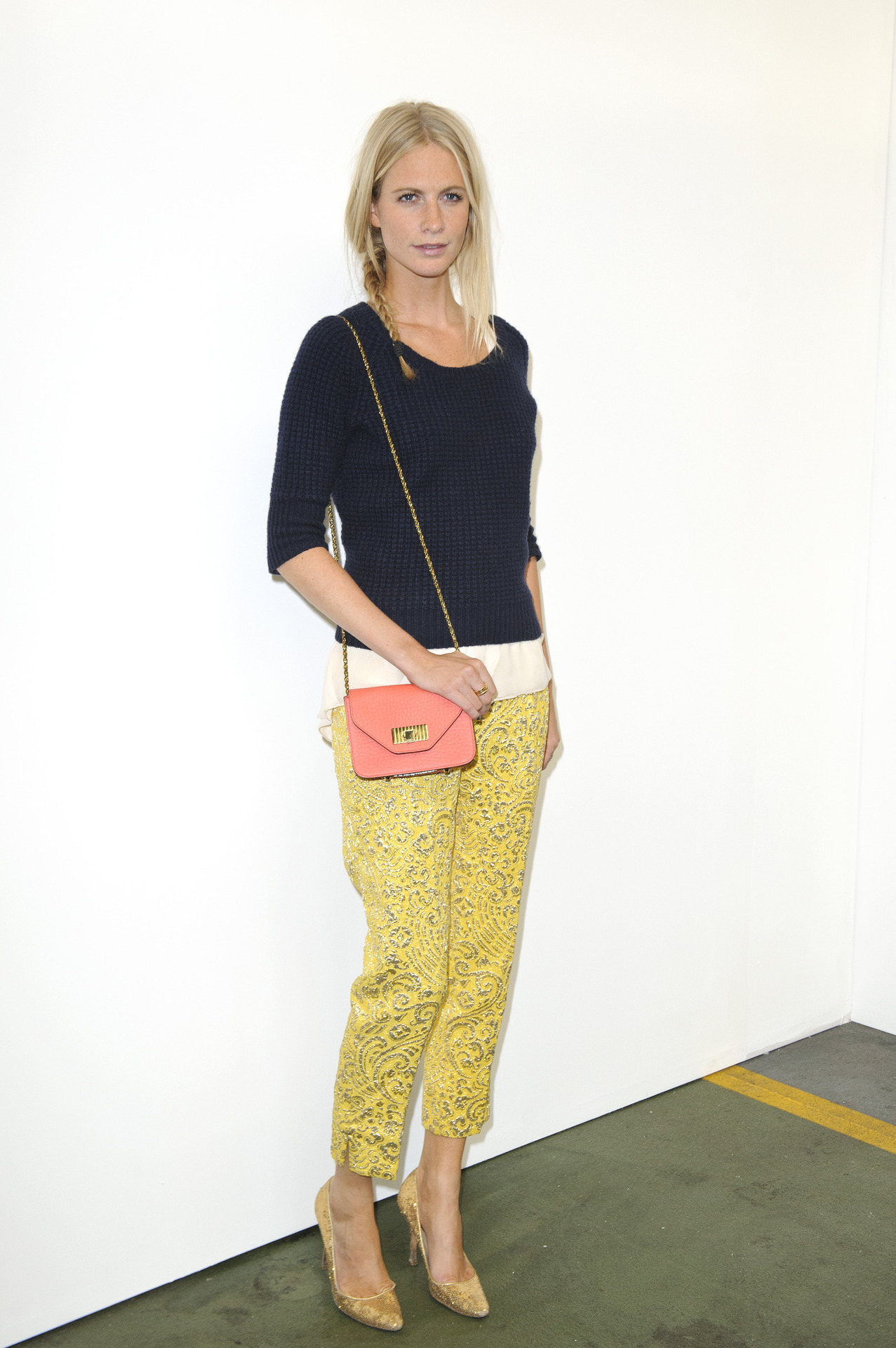 ofthemomentblog:  Poppy Delevingne at House of Holland in yellow brocade trousers, knitted pullover, gold heels and braided hair. It's all about high and low in London!