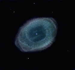 Ring Nebula Drawn Drawing Credit & Copyright: Frédéric Burgeot Explanation: A planetary nebula with a simple symmetry familiar to telescopic sky gazers, the Ring Nebula (M57) is some 2,000 light-years away in the musical constellation Lyra. Hints of changing colors and subtle details are brought out in this remarkable sketch of the cosmic ring. The sketch was made with 800x magnification and excellent seeing conditions directly at the eyepiece of a 40 inch reflecting telescope. Colored pencils on white paper were used to create the original drawing, shown here digitally scanned with an inverted palette applied. About one light-year across, the nebula is composed of outer layers expelled from a dying, once sun-like star. Intense ultraviolet light from the hot central star ionizes atoms in the gas and powers the nebular glow. Ionized hydrogen adds a reddish tint. Ionized oxygen produces a characteristic blue-green color. Difficult to see under average conditions with small telescopes, the Ring Nebula's central star was visible at all times during the artist's study.