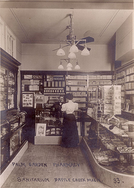 This is What Camera Shops Looked Like a Century Ago Here's a crop that provides a closer look at what's going on:  In the image, we see two shelves with Kodak cameras on display, a Kodak sign in the background, a photo album for sale, a standing postcard rack with photo postcards, and various films and photo supplies on the shelves.