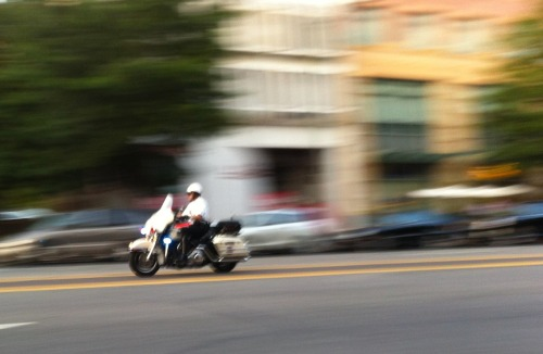 BONUS PHOTO 2: A cop driving up Pennsylvania Ave., as part of a motorcade. Everything I'm reading (on Twitter mostly) is suggesting that it was the Presidential motorcade. Obama was scheduled for a fundraiser at 7 PM, and the photo was taken at 7:05. Other people put up videos of the motorcade driving down the mall, and they were presumably correct in determining who it was; the order of vehicles in their videos matched the order of vehicles I saw. This is all a long way of saying that I think I accidentally almost walked into the President's fundraiser. I saw the motorcade traveling northwest on Pennsylvania and then making a sharp turn onto L Street heading eastward. I then walked a few blocks over, to 24th between L and M. The western side of 24th was completely blocked off by a line of cop motorcycles. People were walking up and down the eastern side. From there, I could see down an alley that there were some tents set up with caterers behind. So presumably the fundraiser is going on in those tents. I was up there to take a look at a Zipcar that I had reserved. The car was parked in a garage in an apartment at 24th and M, which was on the side of the street that was blocked off, and which was right next door to the fundraiser. The door to the apartment, though, was further up the street, so the cops were letting people in and out of the apartment. From the apartment lobby I went down to the garage, found the Zipcar, and—couldn't find my way out. Instead of coming back to the elevator, I ended up walking up through the garage driveway onto the street. Right behind the police blockade. If any of them found it odd that some random guy had just popped up in the cordoned-off area, they didn't say so. I quickly scooted to the other side of the street before they could say anything.