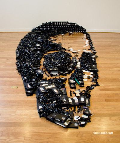 "Happy Halloween and Day of the Dead! Pictured: ""Dead Media,"" an installation that repurposes 497 VHS tapes. Created by friend of Unconsumption Noah Scalin (mentioned previously several times here), of the Skull-A-Day project. (photo via SkullADay here) See also: Other videotape-related repurposing examples in earlier posts here."