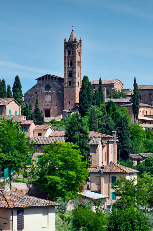 "San Gimignano is a small walled medieval hill town in the province of Siena, Tuscany, north-central Italy. Known as the Town of Fine Towers, San Gimignano is famous for its medieval architecture, unique in the preservation of about a dozen of its tower houses,which, with its hilltop setting and encircling walls form ""an unforgettable skyline"".Within the walls, the well-preserved buildings include notable examples of both Romanesque and Gothic architecture, with outstanding examples of secular buildings as well as churches. The Palazzo Comunale, the Collegiate Church and Church of Sant' Agostino contain frescos, including cycles dating from the 14th and 15th centuries.The ""Historic Centre of San Gimignano"", is a UNESCO World Heritage Site. The town also is known for the white wine, Vernaccia di San Gimignano, produced from the ancient variety of Vernaccia grape which is grown on the sandstone hillsides of the area."