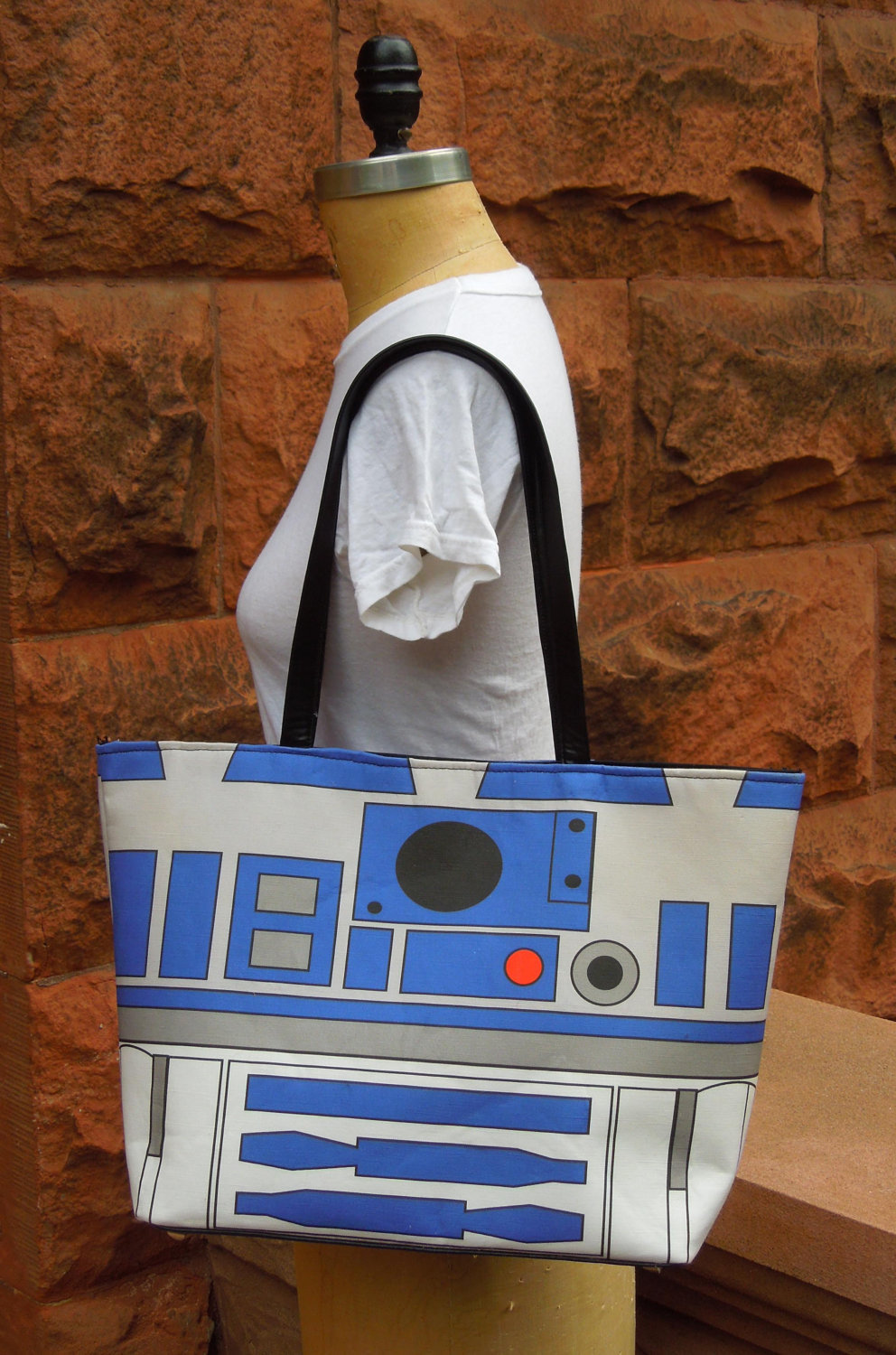 "Large Printed Star Wars R2D2 Handbag with Silver Studded Hardware and Snap Closure  This handbag includes a print I have specially designed and is digitally printed onto the bag. This is not a screenprint. The image on the bag is inspired by R2D2 from Star Wars. It surely makes an impression when worn. This bag is a printed cotton/linen mix and it has some structure to it. The bottom of the bag includes silver studded hardware. Straps and the bottom are high-quality faux leather. Inner pocket with embroidered logo. 1"" Magnetic snap Closure.  (vía OpThreat)"