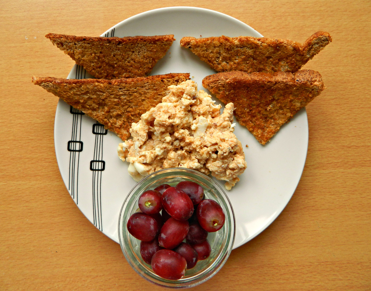 Breakfast - wholewheat toast with soya butter, Italian scrambled eggs and red grapes. (Eggs - 1 whole, 1 white, almond milk, tomato paste, balsamic vinegar, dried basil, paprika - cooked in coconut oil.)