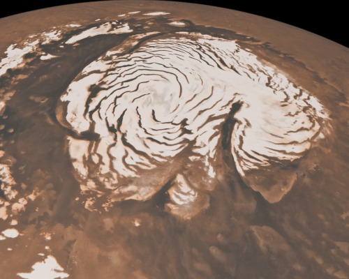 "kinii-noko:  sagan-naut:  It's Snowing on the Red Planet! Bit by bit, feature by feature, Mars is slowly revealing itself to us. A century ago, it was thought of as a planet crisscrossed by a network of canals — surely the great irrigation channels of a highly advanced race. Then we flew by for a first close look in the early 1960s and saw nothing but a cratered wasteland, little better than our own moon, save for the rusty color. But closer study has revealed much more. Mars was indeed once wet, as the dry seabeds and riverways that score its surface attest. Indeed, it still has some water, as new sightings of seasonal streaking down mountain faces caused by springtime ice melt show. Now comes word from NASA's Mars Reconnaissance Orbiter (MRO) that it's snowing on the Red Planet — a lot. A massive, 310-mile-diameter (500 km) cloud persists all winter long over the planet's south polar cap, dumping snow to blizzard-level depths. The catch: this snow isn't made from water crystals, but carbon dioxide, and that's just a little bit of what makes the new findings — and the way they were uncovered— so intriguing.  Don't expect captivating snowflake patterns on Mars, however. Though the scientists aren't certain what shape the falling snow takes, Earth-based experiments suggest they are solid particles — and they're nasty ones too. Catch one of these on your tongue and you've got instant frostbite.This isn't the first snowfall found on Mars; NASA's Phoenix Lander mission detected falling water-ice at the planet's northern regions in 2008. But until now, researchers had only indirect evidence of falling CO2 snow: a bed of CO2 ice on the surface, temperatures cold enough for CO2 to freeze, and satellite-based scans suggesting the presence of dense CO2 clouds. ""We had all those different lines of evidence,"" Hayne says, ""but this is the first direct three-dimensional observation of the cloud and the composition information.""  Read more here  Image Credit: NASA/JPL/Mars Global Surveyor"