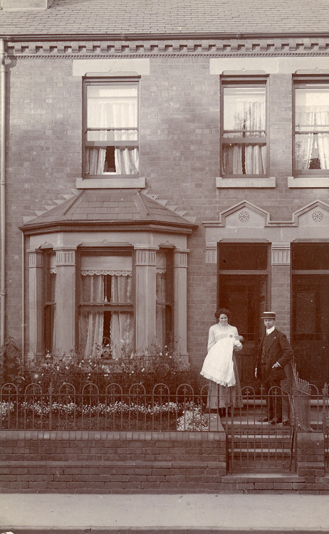 An Edwardian couple with their baby outside the house