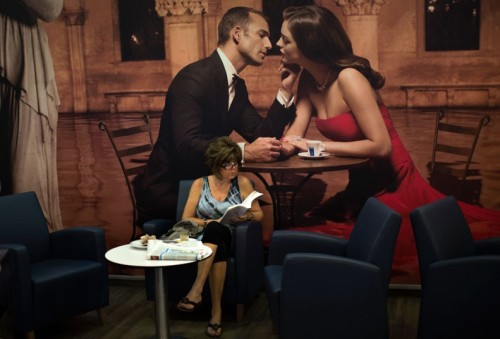 Emilio Morenatti/AP Photo: A woman sits in a cafeteria inside the Barcelona Sants railway station and watches rail workers march during a partial national rail strike. Monday, Sept. 17, 2012.