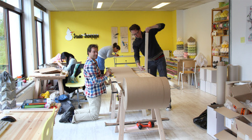 "A day at work in our new studio in ""de Stadhouder"". Here we are working on a simple selfmade tool to cut a roll of paper into paper strips. The logo on the wall has been made by the father of Nellianna."