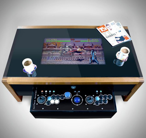 brain-food:  Retro Arcade Table by Surface Tension This wood constructed coffee table comes packed with a built in computer that can be specified to your liking along with 100 licensed games from Midway, Taito, and Atari. The MAME compatibility allows users to play all of their own retro arcade games as well. The 6mm toughened glass reveals your choice of either a 19 inch or 26 inch LCD monitor, while the high quality joystick is concealed within a hidden drawer.   HERMOSO!