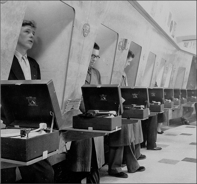 Record Love!  Customers in a record store using listening booths. Oxford street, London.