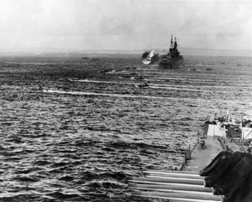 LVTs going in at the battle of Saipan, 15 June 1944. Ship in foreground is USS Birmingham (CL-62); the cruiser firing in the distance is USS Indianapolis (CA-35)