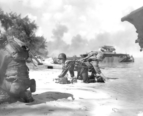 On Saipans beachhead, two Marines keep down low while they crawl to their positions for Japanese fire is whining overhead