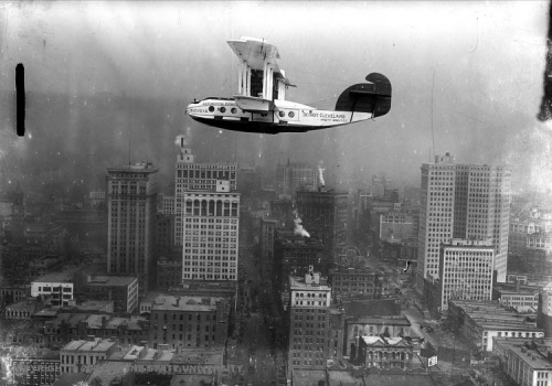 "Commuter biplane flying over Detroit. 1923 Written on plane: ""Aeromarine Airways. Buckeye. Detroit-Cleveland, ninety minutes."""