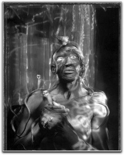 Voodoo Shaman The New York Times Lens Blog profiles photographer Sonia Soberats:  Her subjects are often friends or family, and she frequently captures or recreates life-altering events: pregnancies, marriages, death. Her work is often joyous, but it can be haunting, even schizophrenic. She plays with light and texture and draws on her Latin roots, taking the viewer on a journey to places as magical as the the fictional town of Macondo or as surreal as a Salvador Dalí painting… …Ms. Soberats does not rely on capturing a decisive moment. Instead, her technique, called light painting, involves careful planning and imagination… …Using various light sources, including flashlights and Christmas lights, she darts about the frame like Tinkerbell, illuminating details within the image. The shutter remains open anywhere from two minutes to an hour.  Oh, important note: Sonia Soberats is blind. She's a member of the Seeing With Photography Collective, a New York-based group that creates collaborations between the visually impaired and sighted photographers. Her first solo show was last February in Venezuela. New York Times, Visions of a Blind Photographer. Image: Voodoo Shaman by Sonia Soberats. Via Flickr.