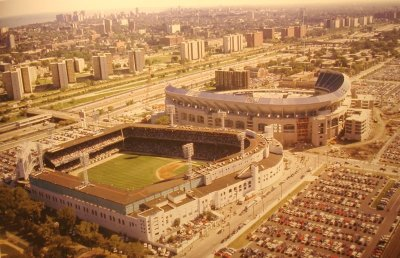 The brief period when Old Comiskey Park and the (almost complete) New Comiskey Park, stood side by side,1990, Chicago. Old Comiskey was demolished in 1991. All that remains now is a marker in the parking lot, showing the former home plate.