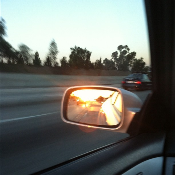 The #sun #sets behind me, as I'm racing down this #road… #mirror #sideviewmirror #car #solara #camry #toyota #nofilter #driving #instgram #sunset (Taken with Instagram at 60 FWY @ Mountain Ave)