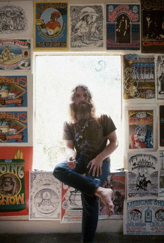 Legendary poster artist Rick Griffin poses in a window surrounded by his work. San Francisco, 1960s.