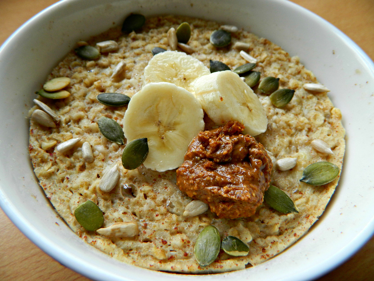 5 Minute 'Baked' Banana Oatmeal! I really fancied some baked oatmeal this morning - but didn't want to wait 30 minutes for it to cook, so made this and zapped it in the microwave instead! :) What you'll need - 1/2 cup oats; 2/3 cup almond milk; 1 egg (or 1 egg white… but cooking time might be longer); 1 banana; A dash of vanilla and cinnamon; A dash of agave or maple syrup if your banana isn't ripe. 1. Mash your banana in to a bowl, then add the egg, agave, vanilla and cinnamon, stirring until combined. It'll look pretty goopy, but don't worry! 2. Add the oats and almond milk, stirring again until combined. Pop in the microwave for 2-3 minutes, cooking on high. Top with any leftover banana slices, almond butter and seeds to make it ~super delicious. :D Stats: 375 calories, 13g protein, 33% of your dietary fibre and 26% of your calcium. Nutritious, quick and filling. Awesome.