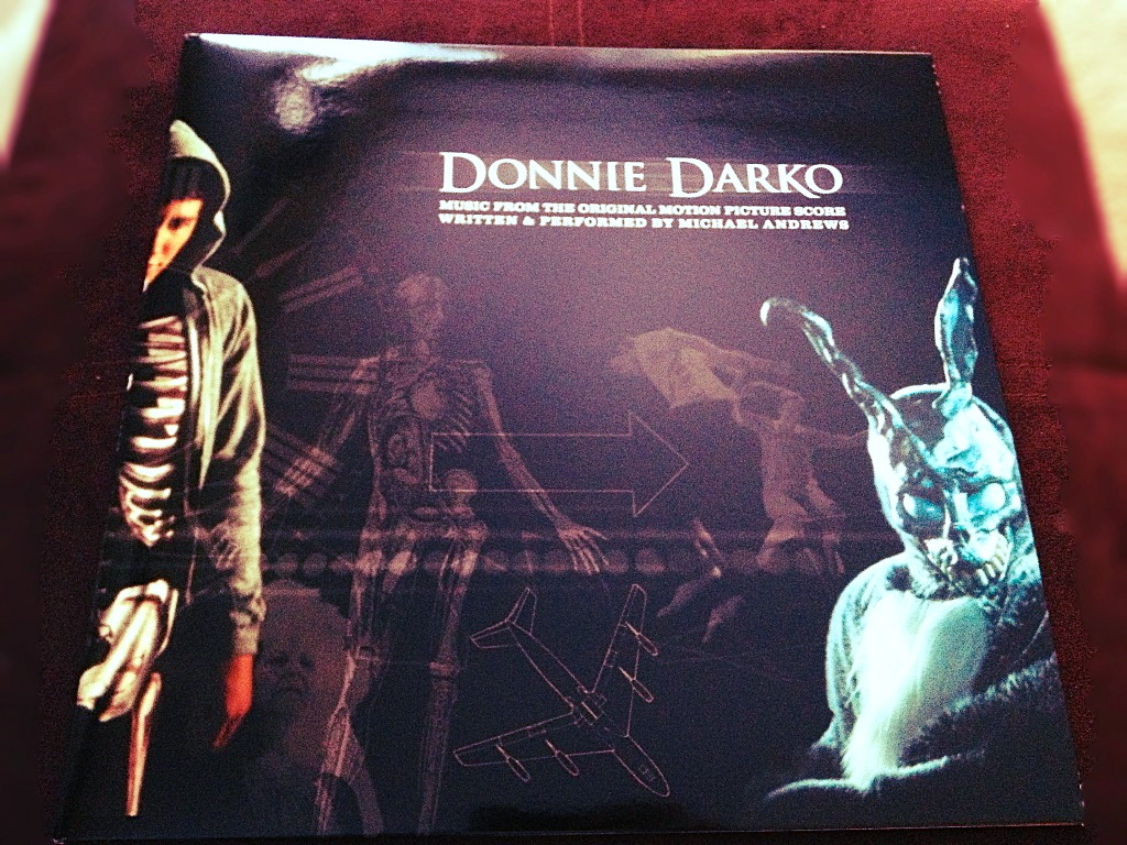 "1recordaday:  Donnie Darko Soundtrack (Black /?) This stands as one of my favorite original score soundtracks of all time. Next to being one of my favorite movies, the score itself is just as haunting as the story. With every composition you are sucked back in to the best scenes from the movie and it somehow manages to give you the same feelings.  The news of this pressing had me elated, being a soundtrack fanatic and all. The packaging is very nice, with a full gloss gatefold jacket accompanying the original score of Michael Andrews, it is a nice collectors piece, as well as something to spin when just aren't quite sure what record to listen to.  The sound quality displays VERY little surface noise, which is just refreshing. The end of the LP features two versions of Gary Jules' cover of ""Mad World"" which is obivously the most famous song from the film. I am proud to say I own this, and every spin is deifneatly an experience within itself."