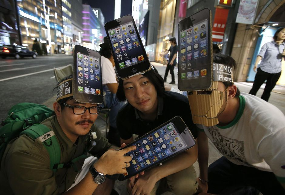 Japanese fans wearing iPhone hats camp outside Apple store in Tokyo(REUTERS/Toru Hanai)