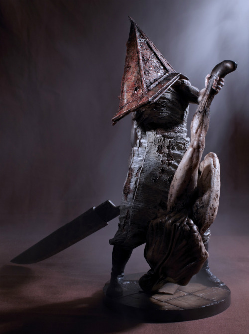 Pyramid Head sculpture, holding a monster from Silent Hill 2.