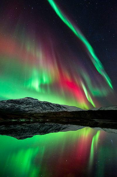 The Aurora Borealis over Høgtuva Mountain in Norway. The Earth's magnetic field funnels particles from the solar wind over the polar regions. More than 80 kilometres above the ground, these collide with molecules in the atmosphere causing them to glow: green and pale red for oxygen and crimson for nitrogen.(caption and image by Tommy Eliassen/Royal Observatory)