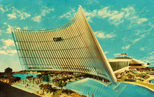 General Motors Futurama Building | NY World's Fair 1964 | Architects: Albert Kahn Associates From OFFICIAL SOUVENIR FLASH CARD SET 1964-1965 NEW YORK WORLD'S FAIR PICTURES  Back of card reads:  The General Motors Futurama Building  The nearly 230,000-square-foot General Motors Futurama building is a landmark for Fair visitors. Entrance to the huge white building is a ten-story-high canopy, constructed of 39 spars rising 110 feet along its face. Behind the canopy, the main portion of the 680-foot-long building houses the exciting 1,700-foot Futurama ride. The building terminates in a dramatic domed pavilion, in which current General Motors cars and other products are displayed. On top of the pavilion, rising the equivalent of eight stories above the ground, is a 40-foot-wide sculpted indicator which revolves, flashing the time and temperature in large illuminated numerals. Source: blog.wanken.com | flickr.com/photos/14696209@N02