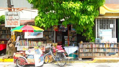 "A Library Grows in Manila Via the BBC:  If you put all the books you own on the street outside your house, you might expect them to disappear in a trice. But one man in Manila tried it - and found that his collection grew. Hernando Guanlao is a sprightly man in his early 60s, with one abiding passion - books. They're his pride and joy, which is just as well because, whether he likes it or not, they seem to be taking over his house. Guanlao, known by his nickname Nanie, has set up an informal library outside his home in central Manila, to encourage his local community to share his joy of reading. The idea is simple. Readers can take as many books as they want, for as long as they want - even permanently. As Guanlao says: ""The only rule is that there are no rules."" It's a policy you might assume would end very quickly - with Guanlao having no books at all. But in fact, in the 12 years he's been running his library - or, in his words, his book club - he's found that his collection has grown rather than diminished, as more and more people donate to the cause. ""It seems to me that the books are speaking to me. That's why it multiplies like that,"" he says with a smile. ""The books are telling me they want to be read… they want to be passed around.""  BBC, The man who turned his home into a public library."