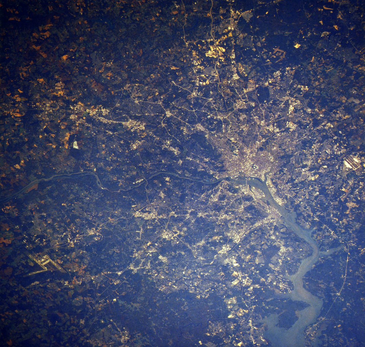 A view of the metropolitan Washington D.C., area from a U.S. Space Shuttle orbiter. The nation's capital is at right center and J.F. Dulles Airport is at lower left. The Potomac River cuts through the center, 10/23/1984