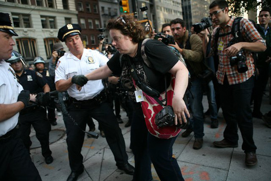 "What's Wrong With This Picture? The story of my #S17 arrest Photographer Julia Reinhart was arrested at #S17 protests, putting the Twitterverse in a tizzy and even being covered at the Gothamist. She gives us her full account at Occupied Stories:  I took one more shot of the cops standing at the corner, when the white shirt officer in charge of the scene pointed at me and said: ""That's it. She's done. Take her,"" and he promptly grabbed my hand. I shouted out that I'm an independent photographer, and showed him my credentials from the National Press Photographers' Association. The officer looked at my badge and said ""they're not ours, so I'm not interested."""