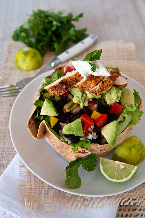 kowaikitty:   Chicken Taco Bowl Salad 2 cups rice - brown rice for a healthier option2 cups black beans2 chicken breasts limes2 avocados  1 onion4 large ripe tomatoes1 red and 1 yellow pepperfresh corn or 1 tin corn kernelsjalepenoslettucehard  cheese (cheddar or Jack)sour creamcilantro/corianderSpices used - coriander, cumin, chili powder, cayenne pepper, smoked paprika, garlic   THE RICE - cook the rice of your choice  and add a splash of lime/lemon juice and sprinkle with chopped cilantro/coriander. THE BEANS - Soak the black beans overnight to reduce the cooking time. Boil them in a pot with a little chicken stock, dash of chili powder, cumin, and cayenne pepper. THE CHICKEN - Slice chicken breasts lengthwise in half and brush with olive oil. Add juice of 1/2 a lemon, 1/4 tsp cumin, 1/4 tsp cayenne, 1/2 tsp chilli powder, 1/4 tsp smoked paprika,  2 cloves crushed garlic,  salt and pepper and cook in skillet until golden THE PEPPERS AND CORN - Cook the peppers and corn in the skillet just to get that chargrilled look but keeping them crunchy. THE GUACOMOLE - 2 avocado, peeled and diced, 1/2 onion, chopped finely,1 teaspoon minced garlic, chopped cilantro/coriander, Juice of 1 lime, Salt and pepper to taste  Chop the avocado, and onion. Add minced garlic, chopped cilantro , lime juice and salt and pepper to taste. THE PICO DE GALLO - 3 ripe tomatoes, chopped finely, 1/2 onion, chopped finely, 2 teaspoon minced garlic, 1 jalepeno chili , Juice of 1 lime, 4 Tablespoons cilantro, plus extra for garnishing, salt and pepper  Chop the tomatoes and allow the juice to drain off. Add the onion, garlic, cilantro, salt and pepper and lime juice.   To Assemble the salad Place taco baskets on a plate and start with shredded iceberg lettuce. Next add the rice, beans, peppers and corn.The Pico de Gallo goes on top of this, and then the Guacamole, and cheese.Add sliced chicken and top with a dollap of sour cream and more cilantro to garnish.  Tempting… I might do it