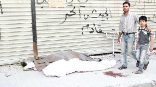 21/09/12 A #Syrian man and a child walk past two bodies laying on the street in the northern Syrian city of Aleppo on Thursday (Sept 20, 2012). Syrians troops backed by helicopter gunships clashed with rebels near an army barracks in Aleppo as pre-dawn battles broke out near a military airport elsewhere in the province, a monitor said.