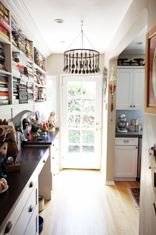 I adore this kitchen—the fork and spoon chandelier, shelves full of books, a cock collection (sorry/not sorry)?! Amazing. photo via the kitchn