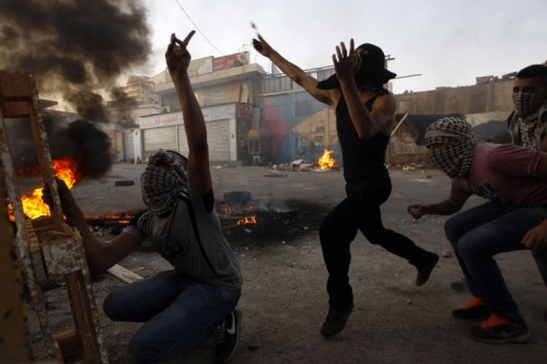 simply-war:  Sept. 18, 2012. Palestinian youths throw stones at Israeli border police (not seen) in the Shuafat refugee camp in the West Bank near Jerusalem. Ammar Awad.