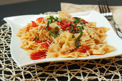 rungmasti:  Baked Tomato Pasta 1/4 c olive oil 1 1/2 pounds cherry tomatoes 1/2 c bread crumbs 1/4 c freshly grated parmesan cheese 1/4 c freshly grated pecorino cheese 2 garlic cloves, finely chopped 1/4 tsp salt 1/4 tsp black pepper 1 pound bowtie pasta (or your favorite shape) 5-6 leaves basil, thinly sliced into strips Preheat oven to 400°F. Pour half of the olive oil into a 13″x9″ baking dish and spread evenly along the bottoms and sides with your fingers or a pastry brush.  Wash cherry tomatoes and pat dry. Slice each tomato in half and place them in the baking dish, skin-side down, to form a single layer in the baking dish. Fit in as many tomatoes as you can. In a small bowl, combine bread crumbs, cheeses, and garlic and mix with a fork. Sprinkle the mixture evenly over the tomatoes. Sprinkle salt & pepper over the tomatoes and bread crumb mixture, and finally, drizzle the remaining olive oil over the top. Place the baking dish in the oven and bake for 20-25 minutes, or until top begins to brown. Once the baking dish is in the oven, bring a large pot of water to a boil. Add pasta and cook to al denté. Ideally, the pasta should be drained immediately before or after the baking dish is removed from the oven. Once you remove the dish, use the back of a large spoon to stir the tomatoes, squishing them to release their juices. Pour the drained pasta into the baking dish and stir well. To slice the basil, stack the leaves together and roll up lengthwise. Then, chop the roll in pieces about 1/8″ wide. Fluff the basil gently with your finger tips and sprinkle over the pasta and tomatoes. Serve with additional parmesan cheese as a garnish. This dish also makes fantastic leftovers!