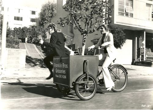 Barbra Streisand and Ryan O'Neal ride a delivery trike.