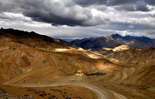 Shades: This view of the Ladakh range near Lamayuru, Ladakh, Jammu and Kashmir, was encountered on my way to Leh. The colors of these ranges keep on changing as the day progresses. The blue shades of the mountains enveloped by clouds afar added to the natural contrast with the golden hue of sun in front. (© Ankur Sharma/National Geographic Photo Contest)