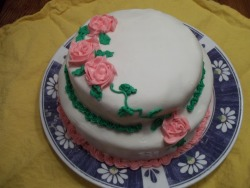 liztrade:  I've never been a huge fondant fan, but when the cake started crumbling when I put the buttercream over it, I had no choice but to make it. This was my first time making marshmallow fondant, and outside of the ordeal when the marshmallows melted and expanded over the pan in the microwave, it wasn't too bad. It tastes really good too. The fondant was a little creased, but you can't see that in the photo. I'm only dissatisfied with my roses. They icing was too soft and they kept falling apart when I tried to move them. I ended up frosting the majority of them on the cake itself.