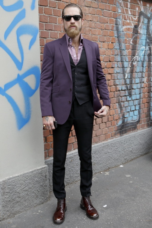 More of Justin O'Shea snapped between #MFW shows, this time wearing a purple 2-button sports jacket and bengal striped two-button collar shirt. The combination of purple tailoring and oxblood red boots injects some unexpected colour into the buying director's signature rocker styling. WGSN street shot, Milan Fashion Week