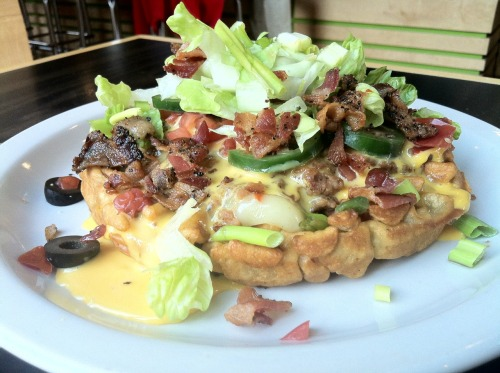 Introducing…Waffle Nachos! House made Belgian waffle covered in Pepper Jack cheese, refried beans, chili, diced olives, jalapeños, and tomatoes, smothered in nacho cheese and topped with a dollop of avocado crema, shredded lettuce, diced bacon and scallions.