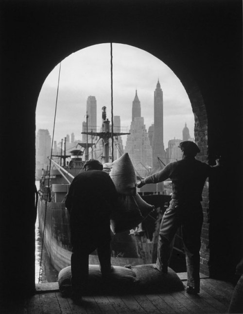 Andreas Feininger Men unload coffee at a Brooklyn dock with Lower Manhattan visible in the background, 1949.