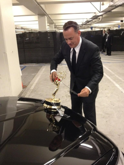buzzfeed:  This is Tom Hanks taping his Emmy to his car. Also, he has a mustache. All around, this is a pretty great picture.  Perfect.