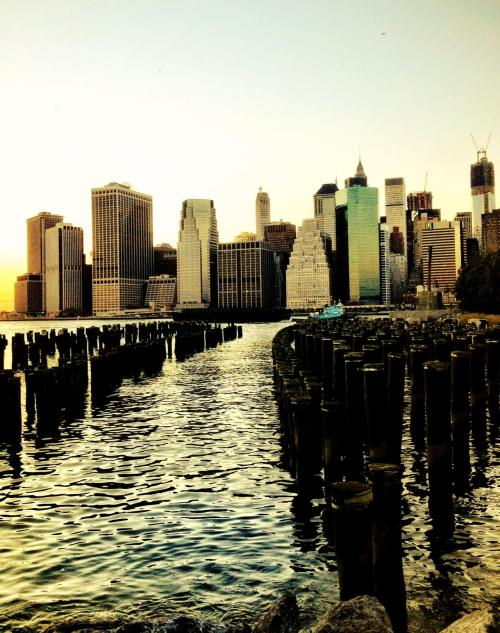 "The New York City skyline. Brooklyn Bridge Park.  The soft light of the sun rises slowly kissing the horizon before ascending into the sky.   And the city, awash in the sleepy glow of night's embrace, glistens in the bleary-eyed blink of dawn's eye.  —-  This photo was taken with my phone and edited with Camera +. I am @newyorklens on Instagram (view my feed here).  Check out my other  phone photography posts made to this blog, and my mobile photography photos on Flickr.  —-  View this photo larger and on black on my Google Plus page   —-  Buy ""New York City Skyline"" Prints here, My mobile photography for sale here, My regular photography for sale here, email me, or ask for help."