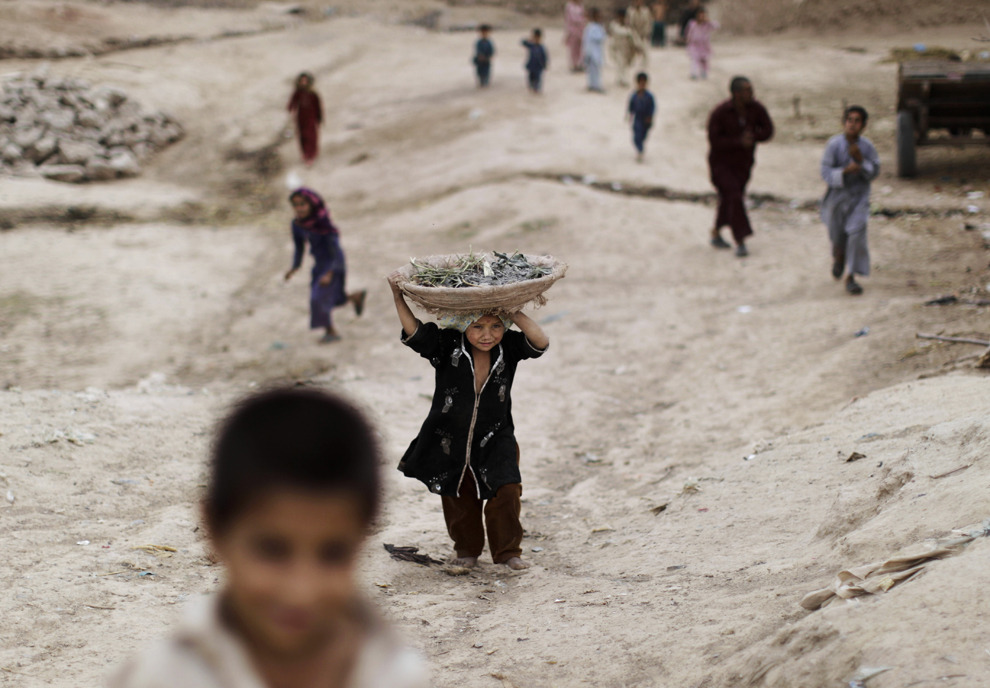An Afghan refugee girl returns home carrying a basket in a slum area on the outskirts of Islamabad, May 7, 2012. (Muhammed Muheisen/Associated Press) #