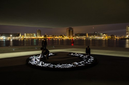 "CRYSTAL by Studio Roosegaarde This interactive installation piece is comprised of 700 small LED rocks which interact with people as the walk across them. They react to both light and sound and actively ""breathe"" while no one is stepping across them. The LED rocks are wirelessly charged by the powermat which they are placed on and users are encouraged to move, swap, and replace the Crystals, which in turn affects the overall breathing pattern of the rocks in their dormant state. A video demonstration is embedded below.  Artists: 