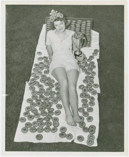 crowcrow:  The doughnut queen, 1940's  SOMEONE TAKE PICTURES OF ME LIKE THIS! PLEASSSSE     I want to be photographed in this pose, surrounded by doughnuts, and I insist that the resulting photo be used for my obituary.