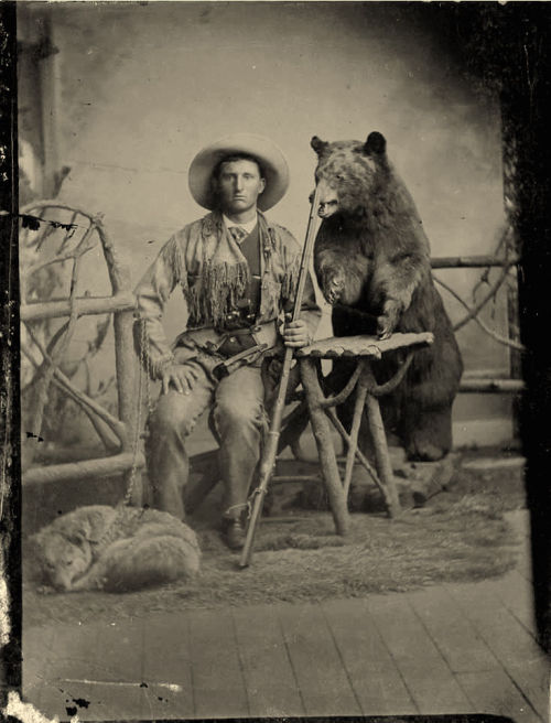ca. 1860-80's, [tintype portrait of a hunter and his dog, both sitting with a taxidermied bear looming menacingly behind], *Related: 1, 2 via Heritage Auctions