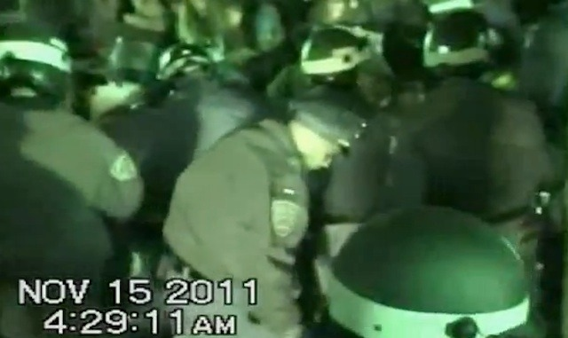 "Updated: Anonymous Leaks NYPD Footage Of Occupy's Eviction From Zuccotti Park  Anonymous has leaked what they claim to be ""hours"" of footage of last year's raid on Zuccotti Park shot by the NYPD from 14 different cameras. A short montage of the footage has been compiled together for a YouTube video, but the file available for download is 11 GB. ""While it's clear that a lot of this police footage is incomplete and has been edited, some may say even tampered with, to remove the most damning incidents (sometimes in very obvious edits),"" the uploader writes, ""there is still enough material to paint the picture of what really happened in Zuccotti park once the media cameras have left.""  The footage shows helmeted NYPD officers making arrests, some sort of device discharging a large amount of smoke in front of an officer, and officers wielding a saw to cut into metal that is securing a protester to a tree (some protesters used bike locks to prevent themselves from being removed from the park).  An email to the NYPD's top press spokesman, Paul Browne, has not been returned. Previously, very little footage of the November 15th raid existed because the NYPD forced media away from Zuccotti Park. Footage of the mass arrests during the Brooklyn Bridge action taken by the department's Tactical Assistance Response Unit was released as evidence in the subsequent trials against the demonstrators.  [UPDATE] As some keen reporters have noted, there's a good chance this video wasn't ""leaked"" by Anonymous, but rather turned over by the City during the discovery phases in the cases of individual protesters who were arrested during the raid. ""I can confirm that TARU video and other video arising from the November 15th eviction was turned over to defense attorneys,"" says Gideon Oliver, the president of the National Lawyers Guild—New York Chapter. ""That happened some time ago."" The NLG is representing some protesters who were arrested in the raid. Oliver adds that none of the cases have gone to trial yet."