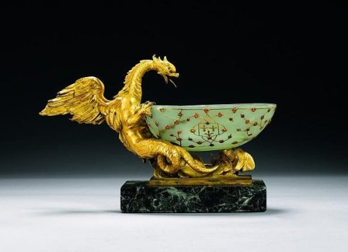 "timur-i-lang:  ""The jade cup was carved from a piece of pale green jade and adorned with a gold vegetable motif in which stems are interlaced with golden rosettes and palm leafs. The agate cup is unadorned. They were acquired by Baron Lionel de Rothschild (1808-97 CE) and have been in his family's possession since that time. On one side of the Jade cup, the application exhibits the Kingdom of Navarre's coat of arms, the so-called Chains of Navarre. The coat of arms of the Bourbons and of the French royal family, on the other side, helps to provide historical context for the object, or at least for a part of it, given that the gilt-bronze mounts appear to be attributable to the nineteenth-century English artisan Benjamin Vulliamy (1780-1854 CE). The elaboration of jade was very highly prized during the period of the Mughal Empire. The emperor Jahangir (1605-27 CE) possessed an extensive collection, part of which had previously belonged to his Timurid ancestors, and he sponsored the production of these types of luxury items. Many of them mimic the forms of older examples. During the seventeenth century it was common for vessels carved from stone to be adorned with gold filigrees and precious stones in the form of vegetable motifs. Some of these decorations recall Western prototypes due to the presence of European lapidaries working for the Mughal court. It is likely that this piece was created for someone in Europe. It is easy to conclude, given the presence of the coat of arms, that it was intended for the King of France himself, and it may have been commissioned directly by one of his representatives. It is also possible that it was a gift of state presented to the king by an ambassador."""